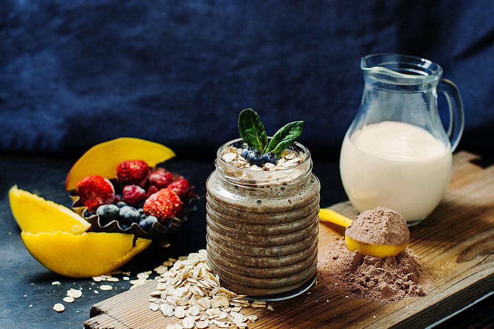 Mango, strawberries, whey protein powder, almond milk, oats, spinach, blueberries and raspberries smoothie