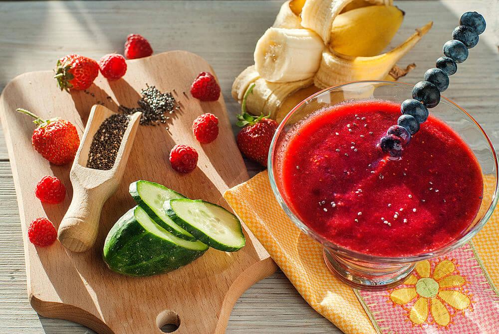 Water, cucumber, strawberries, blueberries, raspberries, chia seeds and banana smoothie