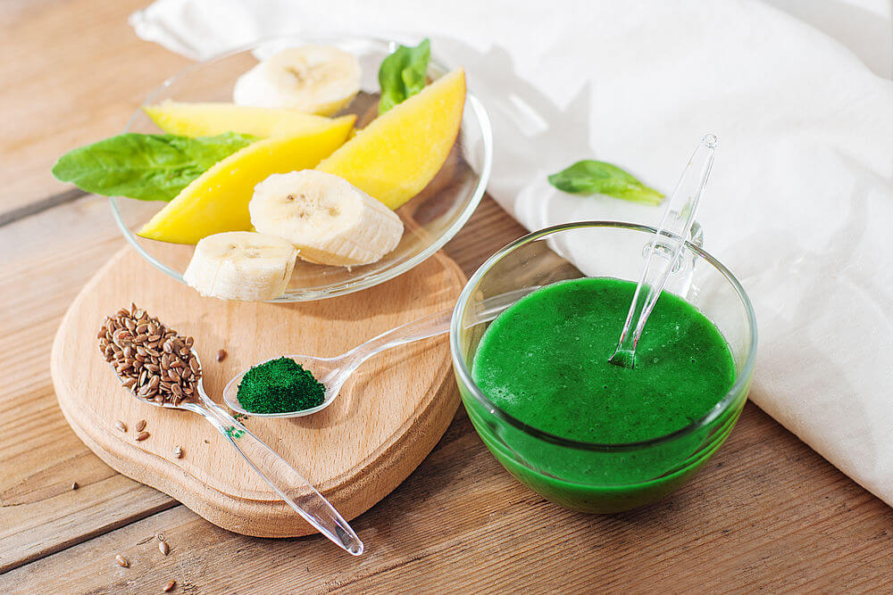Banana, spinach, mango, coconut milk, spirulina, flax seeds and coconut water smoothie